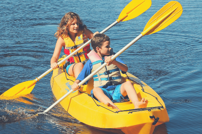 Brother and sister having fun in a sit-on-top kayak.