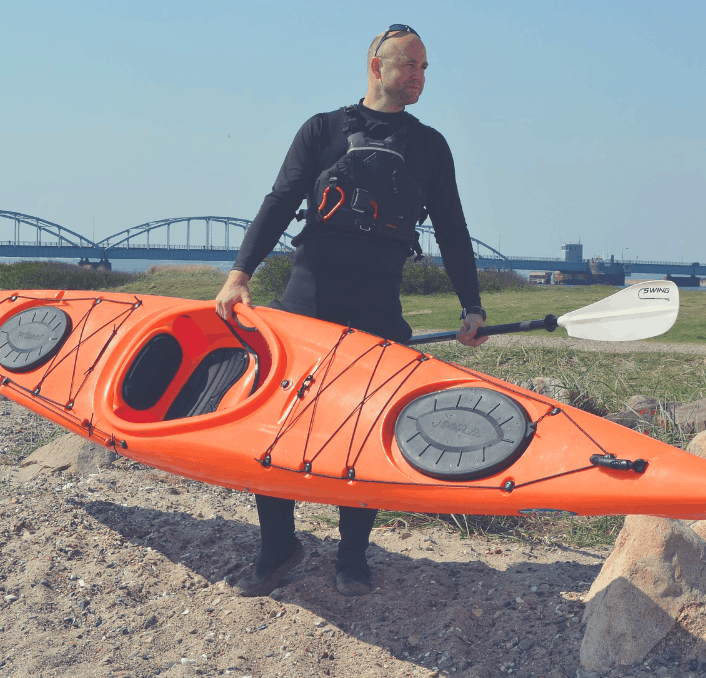 Man with a kayak in his hand.