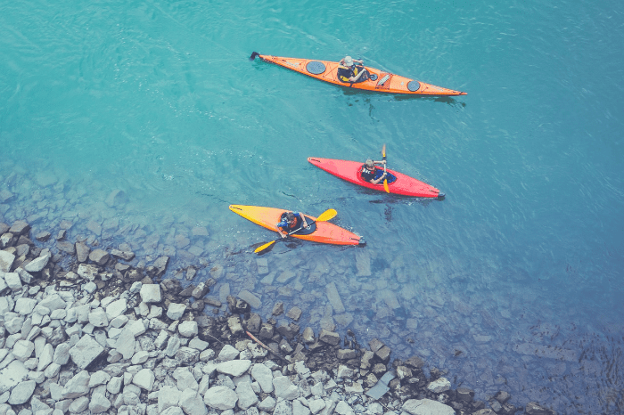 three people kayaking in different kayaks.