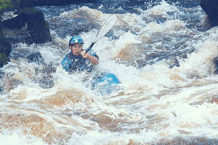 A man kayaking in rapids