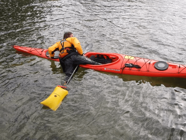 A man using his paddle float to get back in his kayak after capsizing