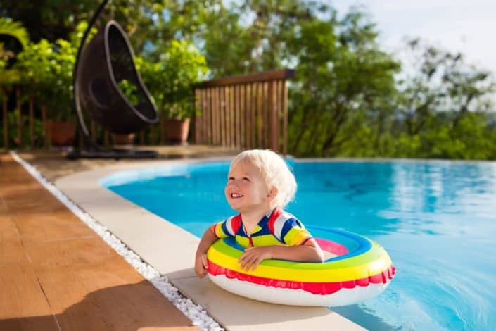 Picture of a kid in the swimming pool, wearing a buoy.