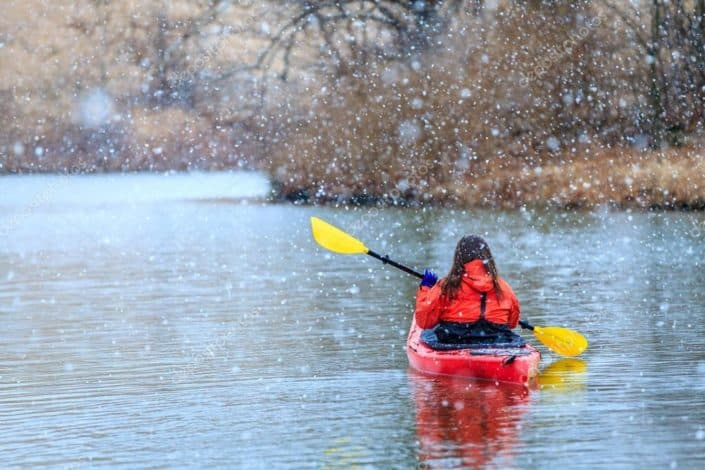a woman kayaking in the snow