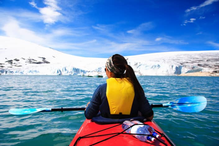 A woman kayaking in the winter cold